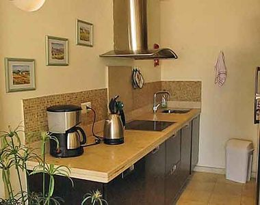Kitchen with ceramic electric hob and coffee maker.