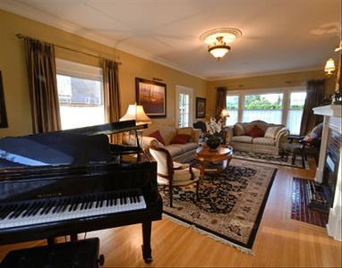 Spacious Living Room with Baby Grand Piano and Fireplace