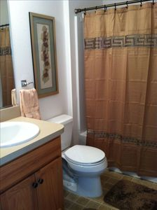 Guest Bathroom w/linen closet has shower/tub with shelves and grab bars