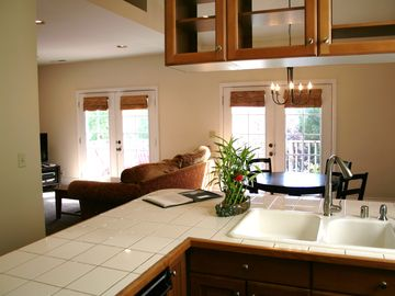 View from kitchen to dining area (right), living area and sunny, bright deck.