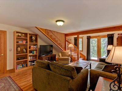"Family room with 47 "" HDTV, couch and love seat.  French doors to deck, hot tub."