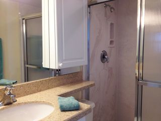 Fort Myers Beach condo photo - Master bathroom- Quartz countertop- Wrap around mirror and inset cabinet- Shower