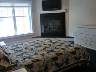 Master bedroom with high definition television and gas fireplace - Alton Bay condo vacation rental photo