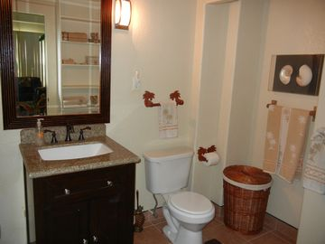 Bathroom with stand-up shower, toilet, towels and all linens.