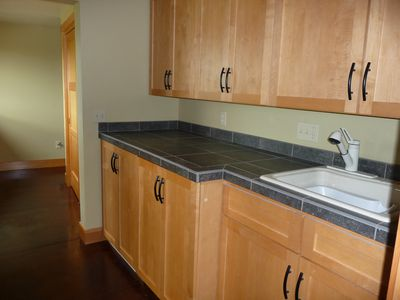 Cabinets containing full-size washer, dryer and laundry sink in main house