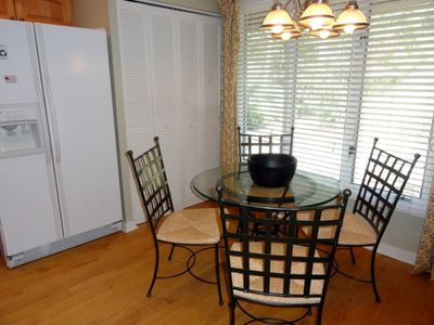 Breakfast table in kitchen. Laundry area is behind louvered doors.