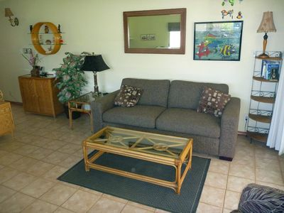 Uncluttered living area features newer queen sofa bed, flat screen TV, DVD.
