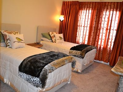 2nd bedroom with twin beds and luxurious bedding. Custom drapes/marble console.
