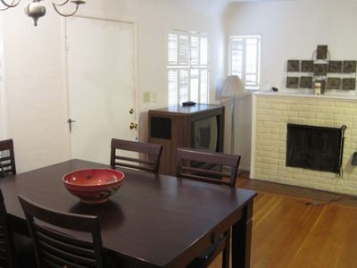 Bright open living room with fireplace, dining room table seats 8 people.