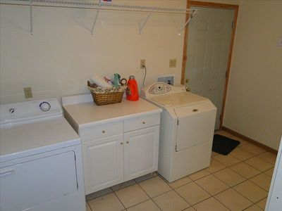 Full size Laundry room with nice appliances and folding table.