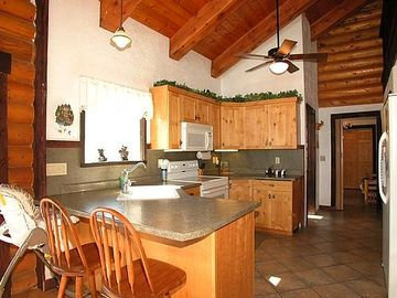 Large kitchen has lots of plates, glasses, pots, and many extra amenities