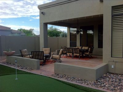 Back yard with lounge and dining outdoor furniture, putting green