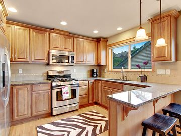 Modern Kitchen with High Granite Counter and Stools for Extra Dining Seating.