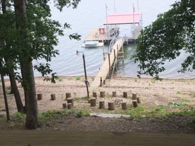 Your private dock and shoreside firepit with log seating viewed from the deck