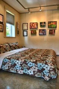 Comox cottage rental - 'The Gallery' suite view of king size bed, and walls of original art