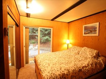 Master bedroom with sliding door out to private deck overlooking firepit.