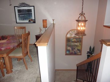 Stairway to - two Master bedrooms. Partial view of dining area.