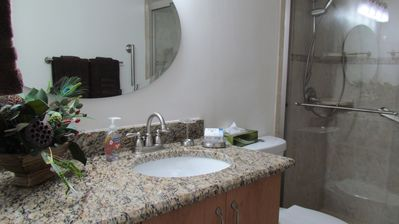 Granite counter and tiled shower