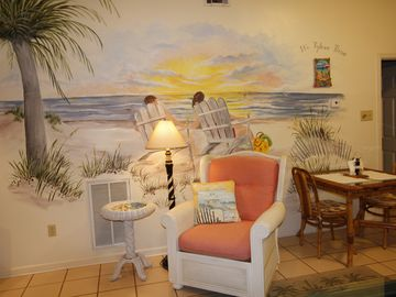 Easy chair in living room with beach mural