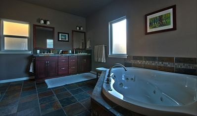 One of two slate-tiled master bathrooms; both have jacuzzi tubs with views