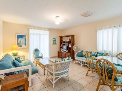 Ground floor living area has comfortable wicker couches and access to the patio