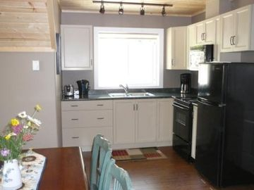The kitchen is fully equipped with dishes, pots & pans, and linens.