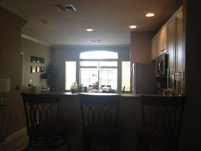 Looking from counter top kitchen bar to dining room