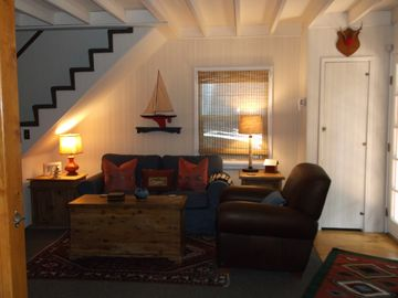 Lake Arrowhead cabin rental - Living room with denim love seat & leather chair. Cozy blankets in cedar chest.