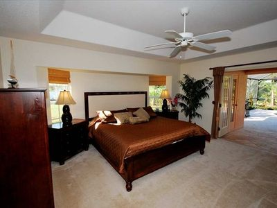 Serene and well appointed master bedroom opens to lanai and swimming pool.