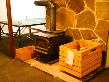 The basement is complete with a cozy wood burning stove and ping pong table.