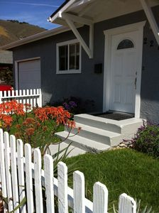 Front view of home with lovely planted yard inside cheerful white picket fence.