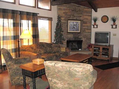 Stacked stone fireplace and beamed ceiling enhance the mountain decor