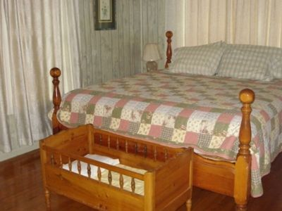 New Braunfels house rental - The master bedroom in the main house features a comfy bed, tv, & hardwood floors