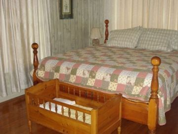 The master bedroom in the main house features a comfy bed, tv, & hardwood floors