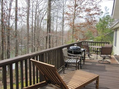 Huge deck with chaise loungers and grill, perfect for entertaining