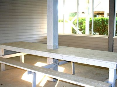 Large picnic table in screened in room under the house