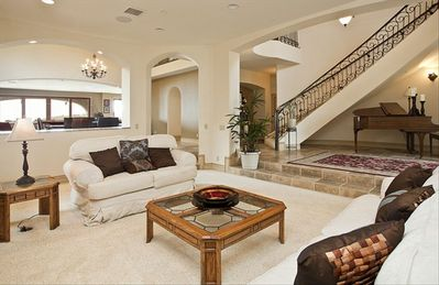 Formal living room and main spiral staircase (one of two in home)