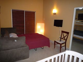 Aruba villa photo - The den with sofa sleeper and TV. Door to kids room with bunk bed and small bath