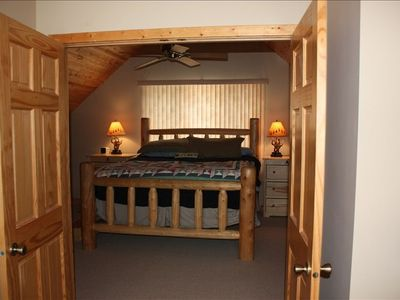 The master bedroom- you can see the stars and the lake from the giant log bed.