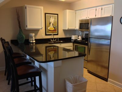 Stainless appliances, updated cabinets and large granite bar serving area
