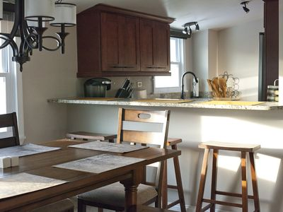 The open concept kitchen is new and furnished with new appliances and cookware.
