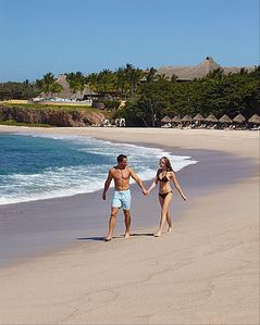 Couple walking on one of Four Season's exclusive beaches.