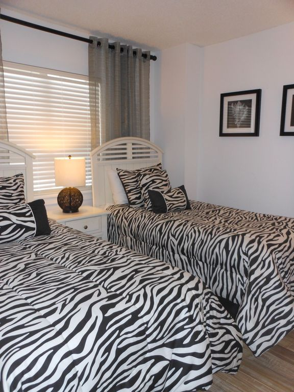 Guest Bedroom with 2 twin beds and hardwood flooring