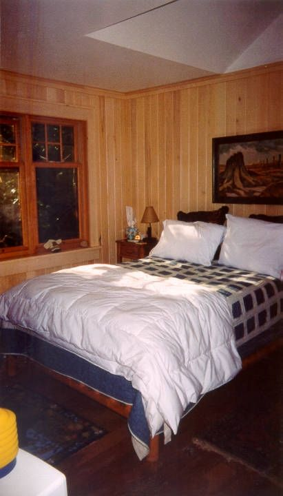 Guest bedroom with window view of conifer woods.