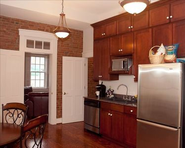 Kitchen with interior brick walls, stainless appliances, and designer cabinets