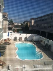 Wildwood condo photo - View of pool from Master Bedroom - 2 grills, tables and chairs available
