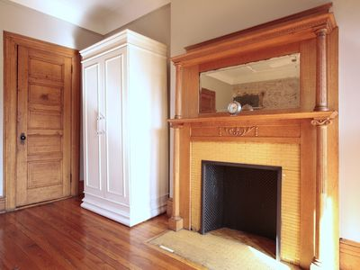 Clothes closet, kitchenette armoire and fireplace.