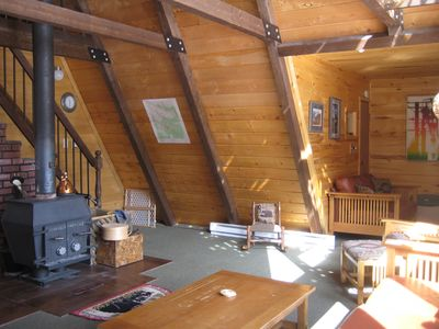 Living room with wood stove, television area, stairs to loft.