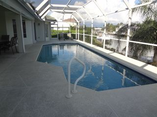 Vacation Homes in Marco Island house photo - Heated pool, eating area, lounging/sunbathing and outdoor pool bathroom