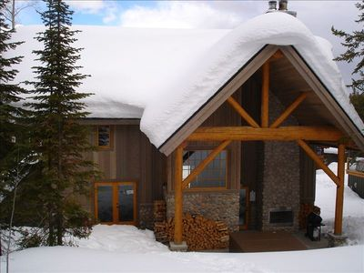 Rear view of Columbia Mountain Lodge patio with  fireplace, hot tub and BBQ